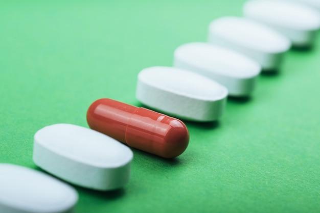Comprimidos brancos médicos e cápsulas marrons para o tratamento e cuidados de saúde em um fundo verde