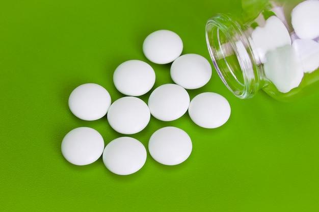Comprimidos brancos são espalhados de uma garrafa de vidro sobre um fundo verde.