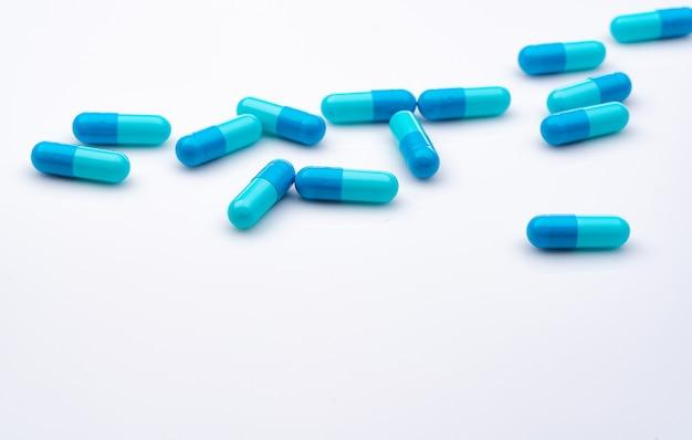 Comprimidos cápsula azul espalhados sobre fundo branco. indústria farmacêutica.