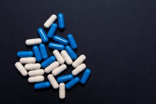 Comprimidos cápsula brancos e azuis em um fundo preto