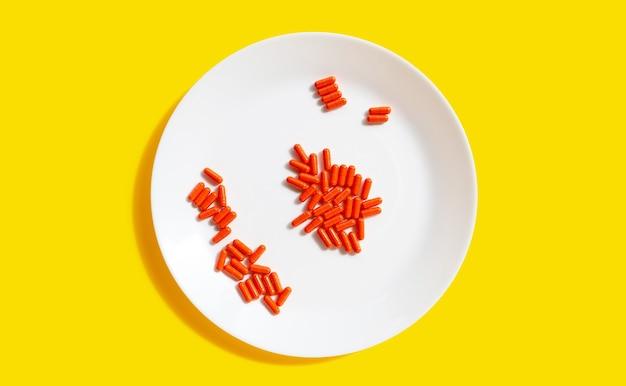 Comprimidos cápsula laranja em chapa branca sobre fundo amarelo.
