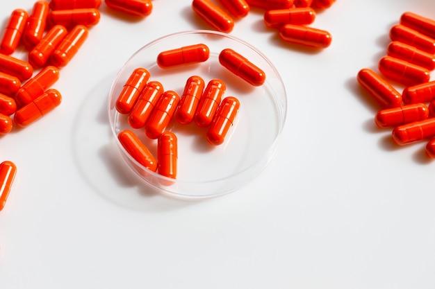Comprimidos cápsula laranja em fundo branco.