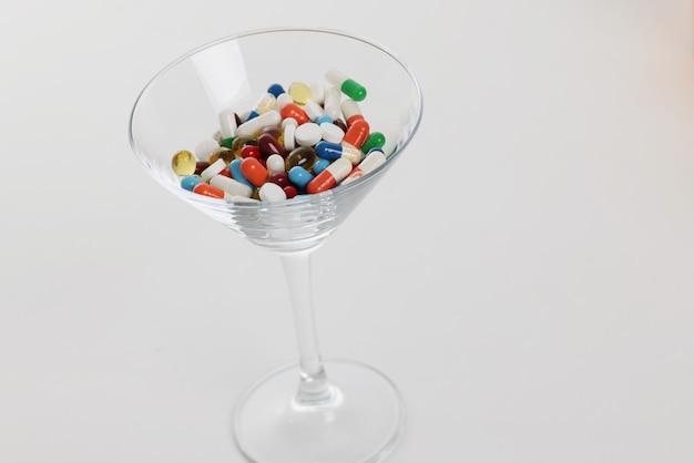Comprimidos cápsula médica multicoloridos em taça de vidro transparente