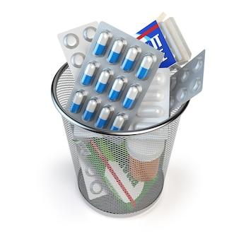 Comprimidos, cápsulas e medicamentos jogados na lata de lixo isolados no branco