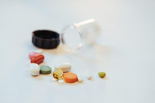 Comprimidos, cápsulas ou suplementos médicos coloridos, para o tratamento e cuidados de saúde em um fundo claro
