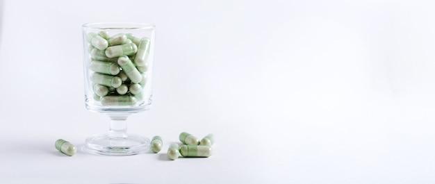 Comprimidos cápsulas verdes em um copo de coquetel em uma superfície branca
