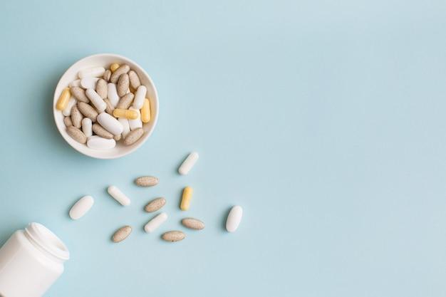 Comprimidos, cápsulas, vitaminas e suplementos alimentares orgânicos naturais em prato branco