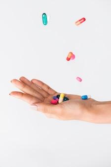 Comprimidos coloridos caindo na palma da mão