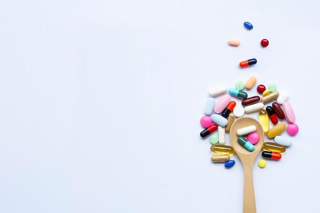Comprimidos coloridos, cápsulas e comprimidos com colher de pau branco
