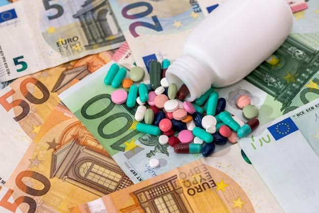 Comprimidos coloridos com recipiente em close up das notas de euro