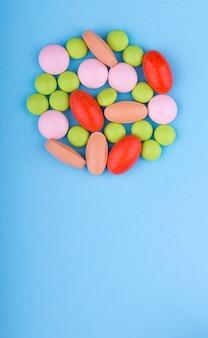 Comprimidos coloridos, comprimidos e cápsulas em uma mesa azul. medicina e saúde.