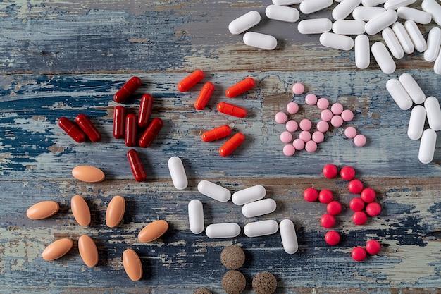 Comprimidos coloridos da medicina sobre o fundo de madeira azul.