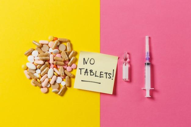 Comprimidos coloridos de medicação dispostos de forma abstrata em fundo rosa amarelo