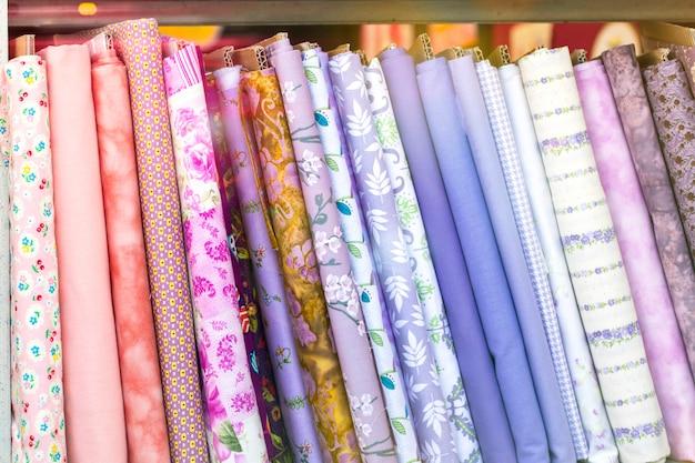 Comprimidos coloridos diferentes de têxteis de tecidos de pano cuidadosamente dobrados para exibição