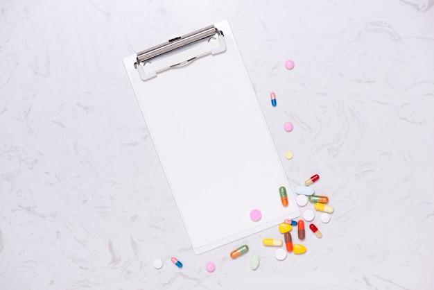Comprimidos coloridos e caderno em branco na mesa. postura plana.