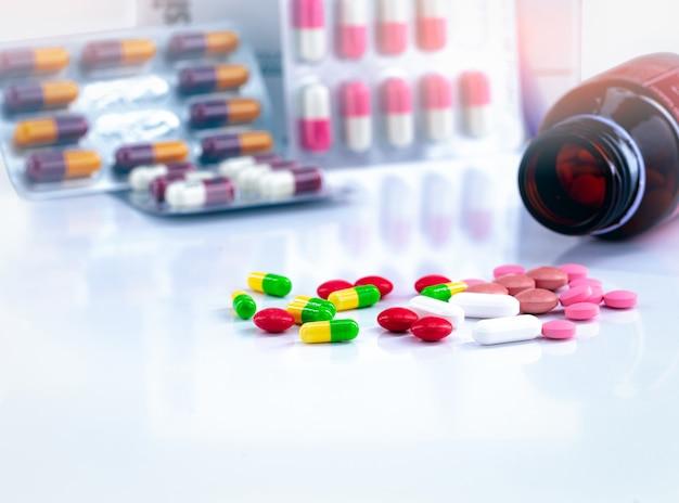 Comprimidos coloridos e cápsulas comprimidos no fundo desfocado do frasco de drogas e antibióticos