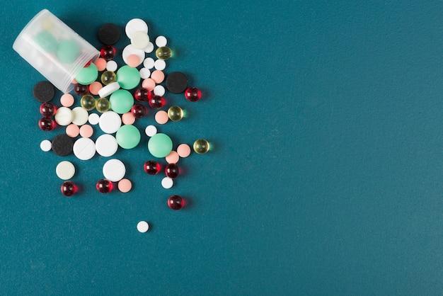 Comprimidos coloridos e copo em azul