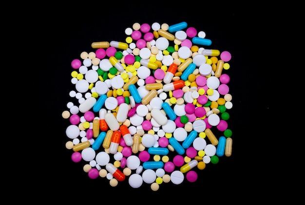 Comprimidos coloridos em um fundo escuro