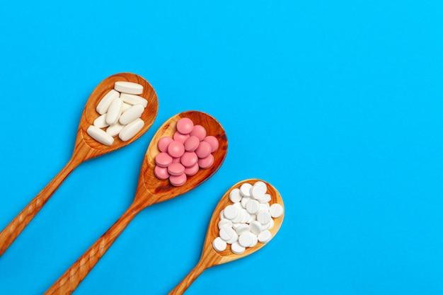 Comprimidos coloridos em uma colher em um fundo azul close-up