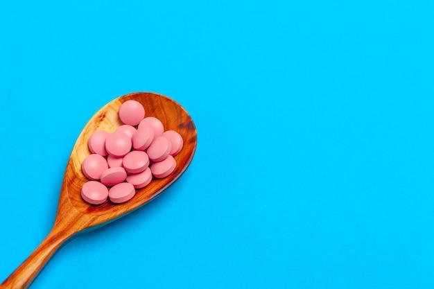 Comprimidos coloridos em uma colher em um fundo de cor close-up