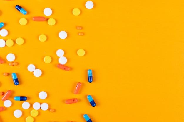 Comprimidos coloridos em uma superfície laranja