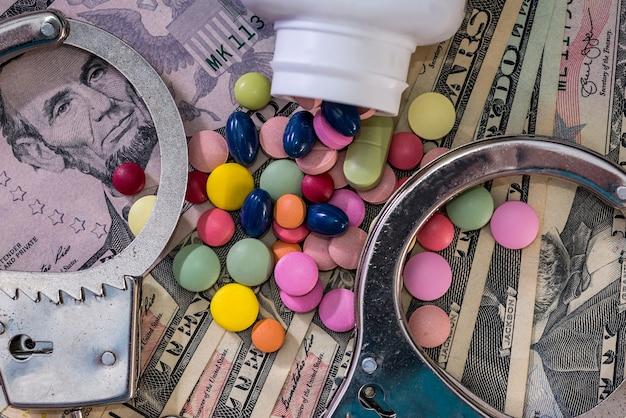 Comprimidos coloridos no fundo do dólar com algemas