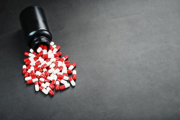 Comprimidos com drogas estão espalhados de um frasco preto sobre um fundo preto.