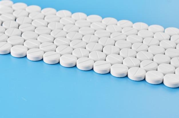 Comprimidos comprimidos cápsulas closeup. sobre um fundo azul, um frasco de remédio.