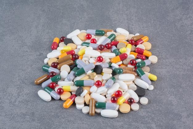Comprimidos, comprimidos e cápsulas de medicamentos farmacêuticos variados.