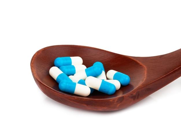 Comprimidos, comprimidos e cápsulas do medicamento na colher de pau, isolados no branco.
