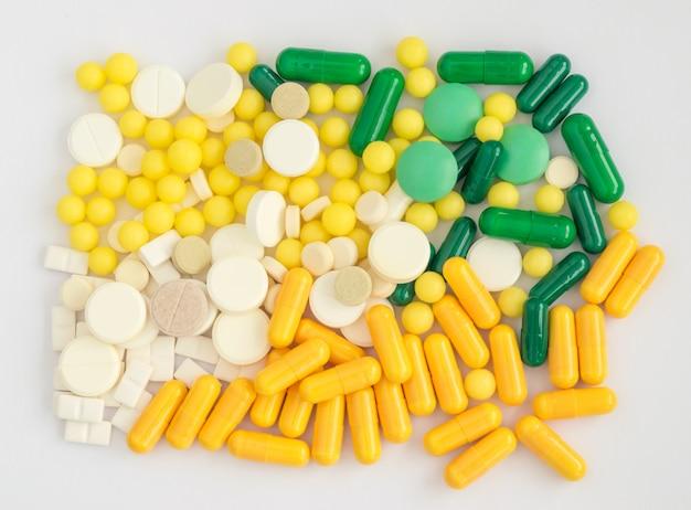 Comprimidos, comprimidos e cápsulas médicas sobre um fundo claro. modelo de farmácia com diferentes tipos de medicamentos