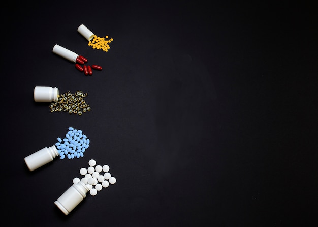 Comprimidos, comprimidos e cápsulas médicos diferentes em um preto