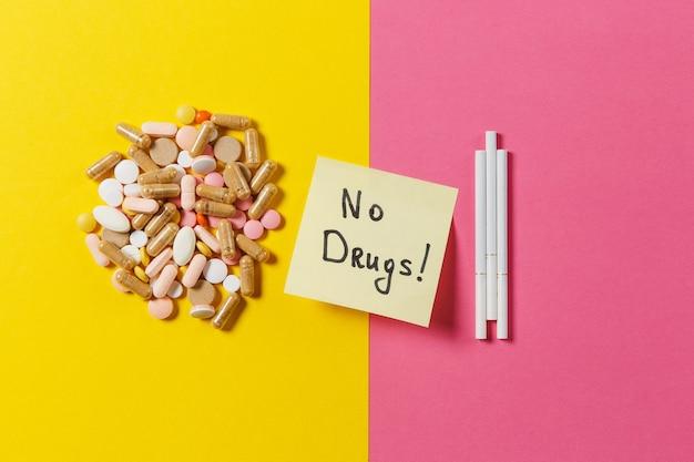 Comprimidos comprimidos redondos coloridos brancos de medicação dispostos três cigarros abstratos em um fundo de cor amarela. palavra de texto de folha de adesivo de papel sem drogas. tratamento, escolha de estilo de vida saudável. copie o espaço.