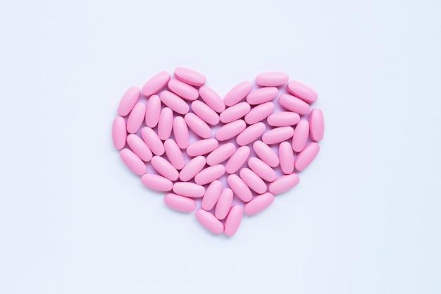 Comprimidos cor-de-rosa da medicina no fundo branco.