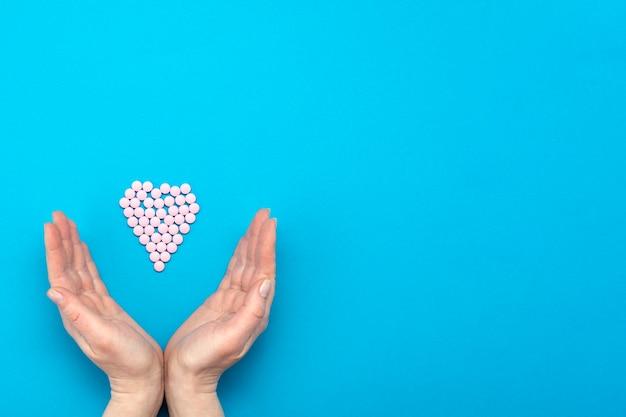 Comprimidos cor de rosa em forma de coração sobre fundo azul e mãos femininas cercam um coração feito de comprimidos.