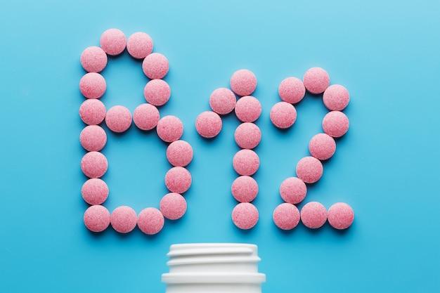 Comprimidos cor-de-rosa na forma da letra b12 em um fundo azul