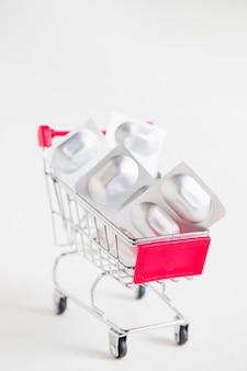 Comprimidos da bolha da tira no carrinho de compras diminuto no fundo branco