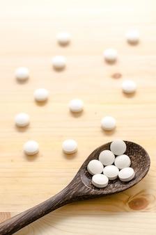 Comprimidos da medicina e colher de madeira no fundo de madeira