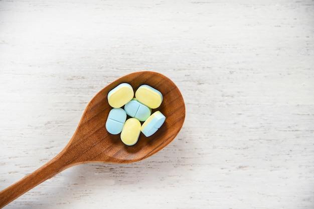 Comprimidos da medicina na colher de madeira na farmácia de madeira branca