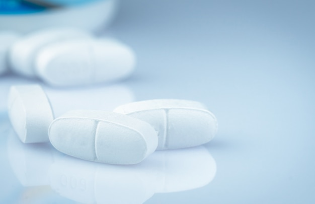 Comprimidos de cálcio para crianças ou mulheres grávidas. comprimidos de comprimidos brancos sobre fundo de garrafa de drogas turva. vitaminas e conceito de suplemento. indústria farmacêutica. produtos de farmácia. saúde global.