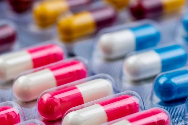 Comprimidos de cápsulas antibióticas coloridas em blister. indústria farmacêutica.