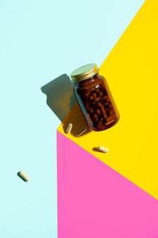 Comprimidos de cápsulas de vitamina magnésio em frasco de vidro em fundo amarelo rosa azulado com sombras da moda