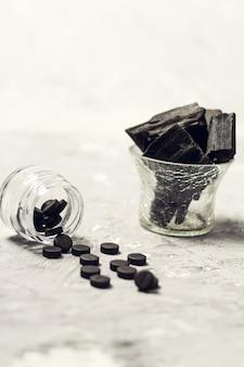 Comprimidos de carvão e carvão ativado na mesa