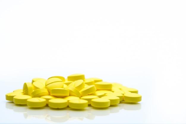 Comprimidos de comprimidos amarelos isolados no fundo branco, com espaço de cópia