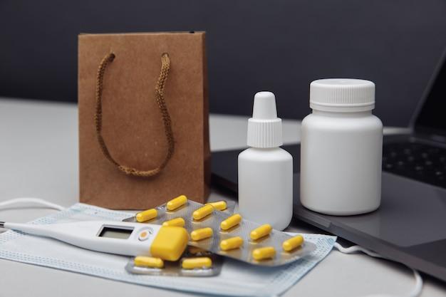 Comprimidos de conceito de compra de farmácia online, termômetro e recipientes de spray e sacos de papel amarelo no laptop close up