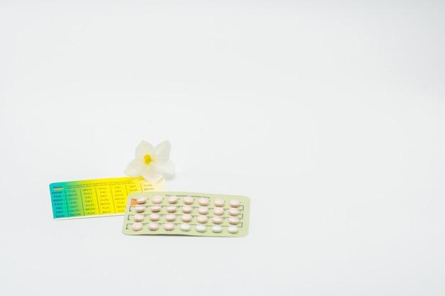 Comprimidos de controlo da natalidade ou comprimido contraceptivo com caixa de papel e flor branca no fundo branco. conceito de planejamento familiar. terapia de reposição hormonal. tratamento hormonal da acne com pílula anti-androgênica.