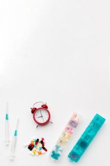 Comprimidos de cópia-espaço com pílulas e relógio