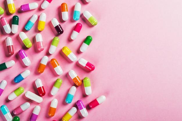 Comprimidos de cores diferentes em fundo rosa