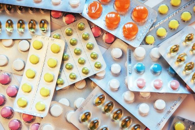 Comprimidos de cores diferentes estão na superfície em uma embalagem selada