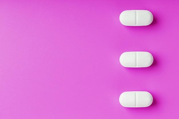 Comprimidos de ecstasy brancos em uma linha isolada de superfície rosa